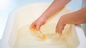 Close-upbeeld van jonge het geven moeder het vullen babybadkuip en het controleren van watertemperatuur royalty-vrije stock foto