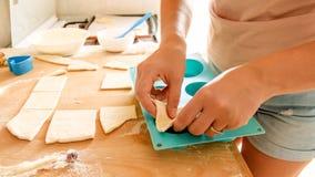 Close-upbeeld van jonge vrouw die stuk van deeg opnemen en het zetten in siliconevorm voor baksel in oven Huisvrouw stock foto's