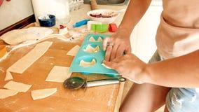 Close-upbeeld van jonge vrouw die stuk van deeg opnemen en het zetten in siliconevorm voor baksel in oven Huisvrouw royalty-vrije stock afbeelding