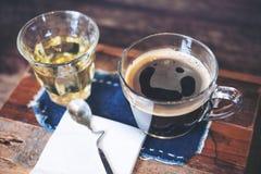 Close-upbeeld van koppen van hete koffie en thee op uitstekende houten lijst in koffie met onduidelijk beeldvrouw die slimme tele Stock Foto