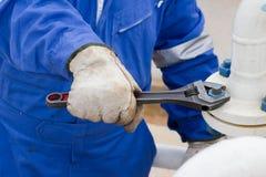 Close-upbeeld van menselijke van het hand het bevestigen en einde lekflens door moersleutel Stock Afbeelding