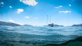Close-upbeeld van overzeese golven en vastgelegd jacht tegen mooie bergen bij heldere zonnige dag stock foto