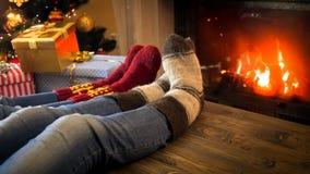 Close-upbeeld van paar die wollen sokken dragen die door de brandende open haard op Kerstmisvooravond ontspannen royalty-vrije stock foto