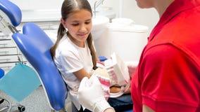 Close-upbeeld van tandarts die haar patiënt over tandhygiëne opleiden stock foto's