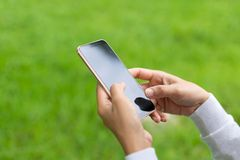 Close-upbeeld van vrouwenhanden die smartphone, Hand van vrouw die smartphone op groene achtergrond gebruiken, het Zoeken of soci stock foto's
