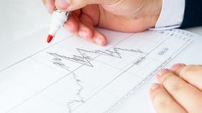 Close-upbeeld van zakenman die rode teller op financiële grafiek gebruiken te schrijven royalty-vrije stock afbeelding