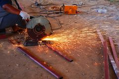 Close-upbeelden van de handen die van mensen die staalsnijmachines met behulp van, over bouw op industriezones vonken stock foto's