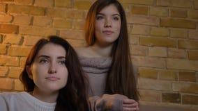Close-upbottom up portret van twee jonge mooie vrouwen die op TV in een comfortabele flat binnen letten royalty-vrije stock fotografie