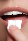 Close-updetail van vrouw die roze kauwgom zetten in haar mond Kauwgom, het Eten, Vrouwen Sluit omhoog op een Mooi Meisje Stock Foto