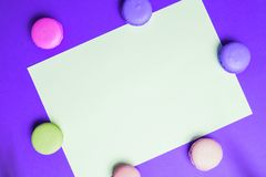 Close-updocument voor exemplaar ruimte, tekst en reclame op purpere achtergrond met multicolored roze en gele makarons stock foto's