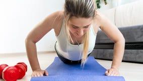 Close-upfoto die van jonge vrouw opdrukoefeningen op geschiktheidsmat thuis doen royalty-vrije stock afbeelding