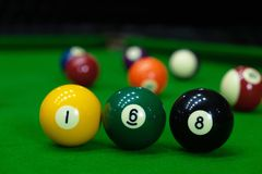 Close-upfoto's, het spelen biljartballen die, diverse aantallen, de bal, de aantallen en de groene grond neersteken stock afbeelding