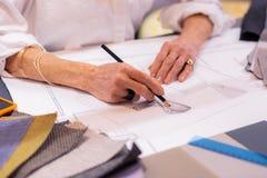 Close-upfoto van bejaarde belangrijke ontwerper die tekening maken bij bureau royalty-vrije stock afbeeldingen