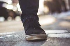 Close-upfoto van de benen van mensen in zwarte tennisschoenen stock foto's