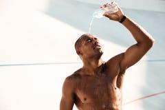 Close-upfoto van de jonge Afrikaanse sportenmens die water uitgieten stock foto