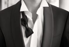 Close-upfoto van de mens in smoking met open overhemd en losse vlinderdas Stock Foto