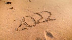 Close-upfoto van 2022 die aantallen op nat zand op het oceaanstrand worden geschreven Concept Nieuwjaar, Kerstmis en reis  royalty-vrije stock afbeeldingen