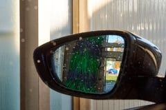Close-upfoto van een achteruitkijkspiegel binnen een autowasserette met wate stock foto's