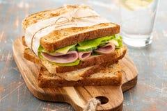 Close-upfoto van een dubbeldekker De sandwich met komt, prosciutto, salami, salade, groenten samen, sla op gesneden vers royalty-vrije stock afbeeldingen