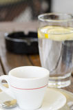 Close-upfoto van een kop van koffie op een schotel met een volgende lepel stock afbeelding