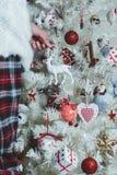 Close-upfoto van jonge vrouw die witte Kerstboom verfraaien bij Royalty-vrije Stock Afbeelding