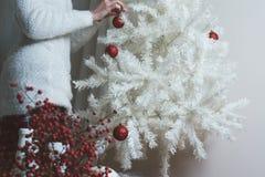 Close-upfoto van jonge vrouw die witte Kerstboom verfraaien bij Stock Afbeeldingen