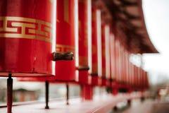 Close-upfoto van rode gebedwielen in boeddhistische tempel Het concept van de godsdienst Boek en kruis stock afbeelding