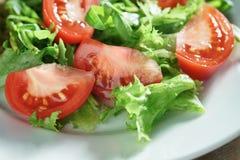 Close-upfoto van verse de zomersalade met tomaten, rucola en frillisbladeren in plaat op houten lijst royalty-vrije stock afbeeldingen