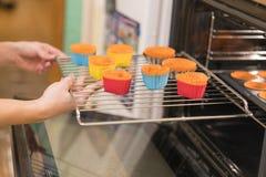 Close-upfoto van vrouw die koekjes in oven zetten De vrouw brengt de ovenkoekjes in de vormen aan royalty-vrije stock afbeeldingen