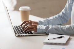 Close-upfoto van vrouwenhanden die op notitieboekje bij Desktop typen stock afbeeldingen