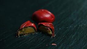 Close-upgeheel en besnoeiing in half klein rood chocoladesuikergoed met karamel het vullen stock video