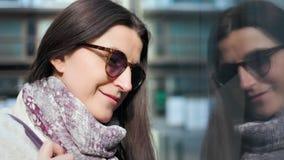 Close-upgezicht het glimlachen vrouw shopaholic het bewonderen glasshowcase van modieuze boutique van straat stock video
