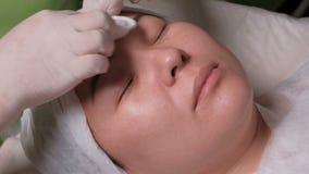 Close-upgezicht van Aziatische vrouw op verjongingsprocedure in een schoonheidssalon De handen van een schoonheidsspecialist in w stock videobeelden