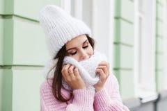Close-upgezicht van een jonge Glimlachende vrouw die van de winter genieten die gebreide sjaal en hoed dragen royalty-vrije stock foto's