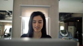 Close-upgezicht van een mooi jong Kaukasisch meisje die op een tredmolen lopen sportenmeisje in zwarte sportkleding Gezonde Leven stock videobeelden