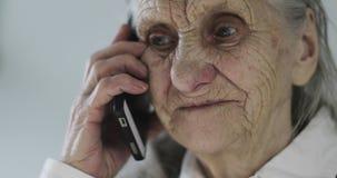 Close-upgezicht van een oude vrouw met diepe rimpels die op een mobiele telefoon in een bureau spreken stock videobeelden