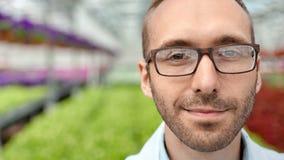 Close-upgezicht van glimlachende mannelijke landbouwingenieur in glazen stellen die camera bekijken stock videobeelden