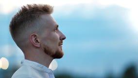 Close-upgezicht van het glimlachen van jonge mens het bewonderen verbazende natuurlijke blauwe hemel bij zonsondergang die op hoo stock video