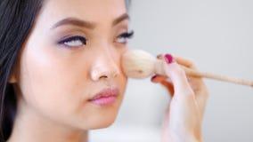 Close-upgezicht van jong aantrekkelijk Koreaans model bij studio terwijl het professionele grimeur werken stock footage
