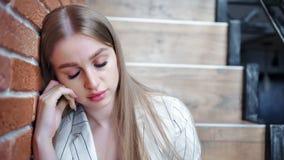Close-upgezicht van teleurgestelde jonge mooie vrouwenzitting op treden bij de achtergrond van de zoldermuur stock footage