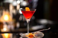 Close-upglas van de cocktail van Manhattan met sinaasappel wordt verfraaid die stock foto