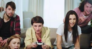 Close-upgroep multi etnische vrienden die een prettijd verzenden samen, twee dames die op een zeer opgewekt videospelletje spelen stock footage