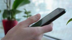 Close-uphand die en een smartphone op vage achtergrond openen houden stock footage