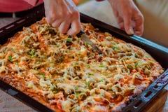 Close-uphand van de scherpe pizza van de chef-kokbakker bij keuken Stock Fotografie