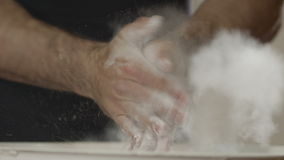 Close-uphanden die met wit krijtpoeder slaan De atleet slaat handen met talkpoeder stock videobeelden