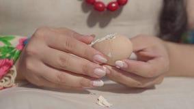 Close-uphanden van niet erkende vrouw in traditionele kleren die het ei van shell schoonmaken die voorbereidingen treffen te eten stock video