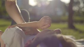 Close-uphanden van oudere zuster die jongere broer in het park kietelen De jongen en meisjes het besteden tijd samen in openlucht stock video