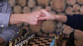 Close-uphanden van schaakspelers, schokhanden vóór of na het spel stock videobeelden