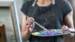 Close-uphanden van vrouwelijke professionele schilder die de acrylverf van de kleurenolie op palet mengen die borstel gebruiken stock video