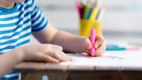 Close-uphanden van weinig creatief beeld van de kindtekening op document die kleurrijke viltpen gebruiken stock videobeelden
